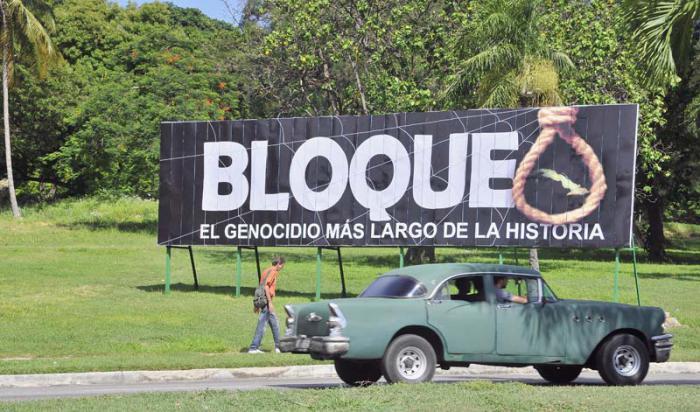 Vehículos por la avenida Boyeros, rumbo a Carlos III. Propaganda condenando el Bloqueo criminal de EEUU a Cuba.