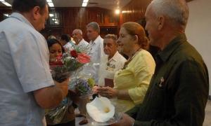Gustavo Rodríguez Rolledo (I), Ministro de Agricultura, entrega flores a condecorados por el 55 Aniversario de la Asociación Nacional de Agricultores Pequeños (ANAP), y el Día del Campesino, en el Acto Nacional celebrado en el Salón de los Vitrales de la