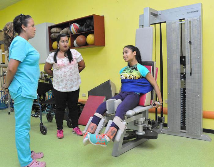 La niña panameña Fatima Moreno Batista, acompañada por su madre (al centro), recibe tratamiento para buscar movilidad en sus extremidades inferiores.