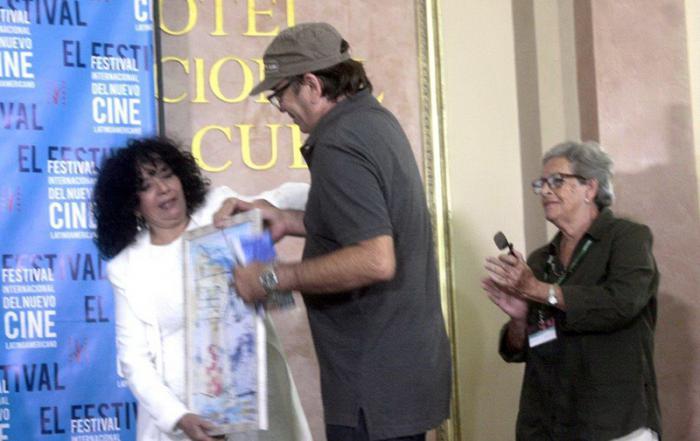 La pintora entrega a Rafael Solís, director de fotografía del documental cubano Gloria City dirigido por Isabel Santos, una de sus pinturas como recompensa por haber sido el premio (colateral) del Circulo de Cultura de la UPEC.