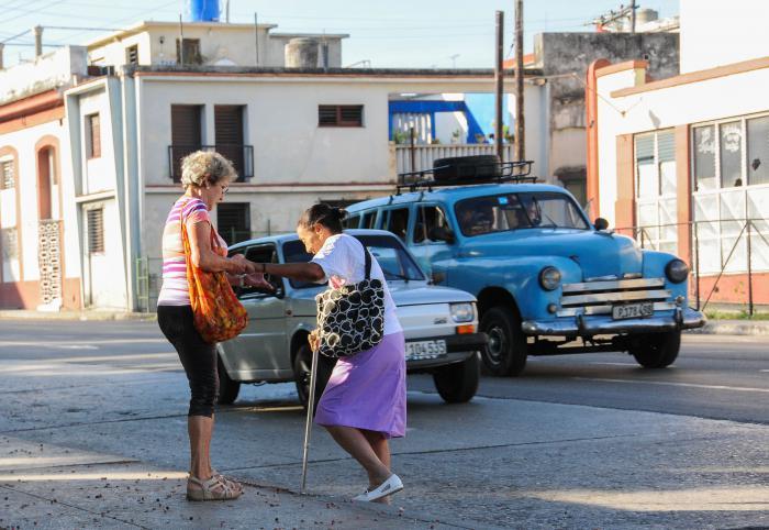 Mujeres de la tercera edad, ayudándose mutuamente en la calle Infanta en el Cerro.