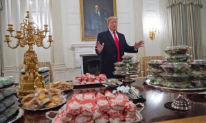 2019-01-15 00:50:15 US President Donald Trump speaks alongside fast food he purchased for a ceremony honoring the 2018 College Football Playoff National Champion Clemson Tigers in the State Dining Room of the White House in Washington, DC, January 14, 201